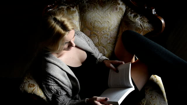 Woman reading book in armchair video