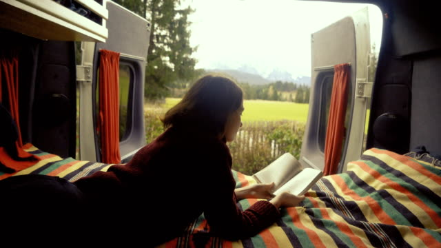 Woman reading book  in camper van with view on Alps Young Caucasian woman reading book in camper van with view on Alps rv interior stock videos & royalty-free footage