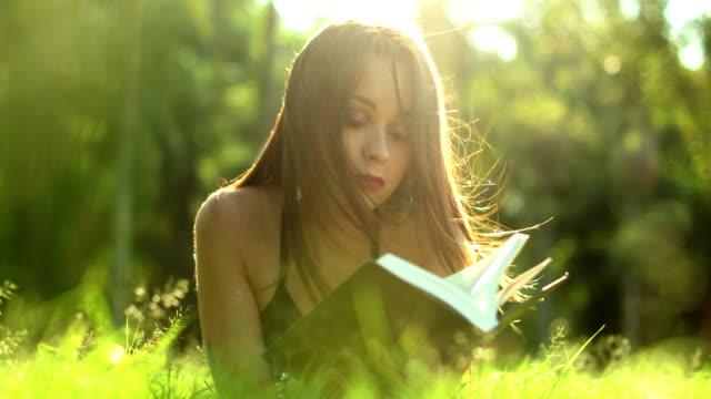 stockvideo's en b-roll-footage met het lezende boek dat van de vrouw in gras bij park ligt. mooi meisje dat van verhaalroman in het zonlicht geniet - literatuur