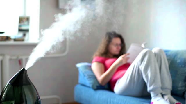 加湿器作業の背景に本を読む女。 - 加湿器点の映像素材/bロール