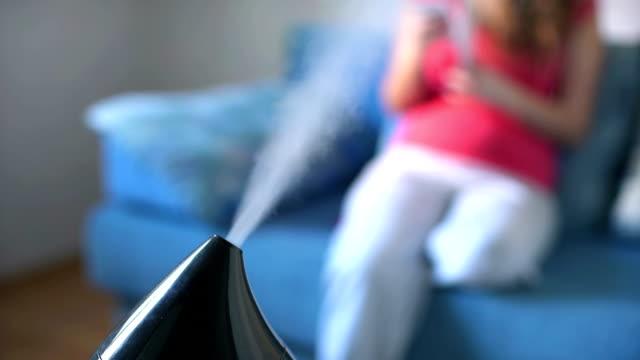 加湿器作業の背景に本を読む女性 - 加湿器点の映像素材/bロール