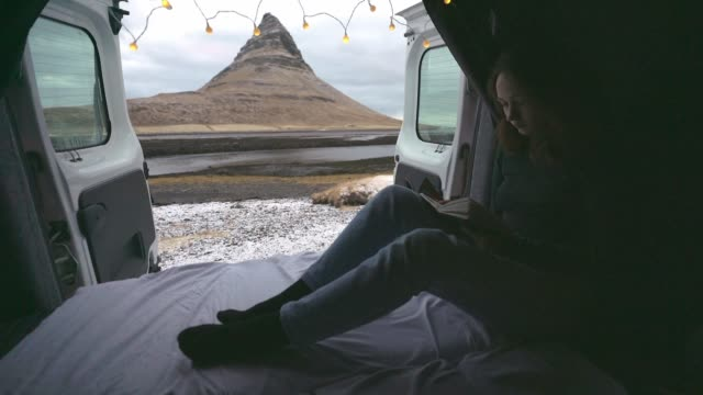 Woman reading in camper van near Kirkjufell mountain in Iceland in winter Young Caucasian woman  reading in camper van near Kirkjufell mountain in Iceland in winter rv interior stock videos & royalty-free footage