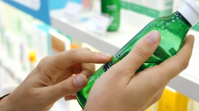 frau lesen etikett auf kosmetikflasche in beauty care shop. - etikett stock-videos und b-roll-filmmaterial