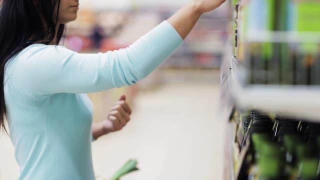 Mujer leyendo la etiqueta de la botella de aceite de oliva en la tienda - vídeo