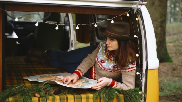 Woman reading map in vintage  camper van Young Caucasian woman in hat  reading map laying in vintagevw camper van rv interior stock videos & royalty-free footage