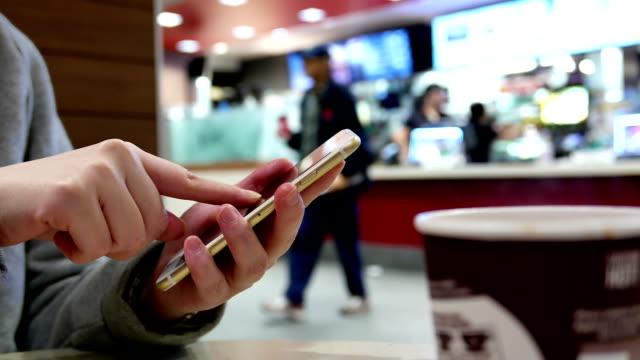 kadın cep telefonunda mesaj okuma - sipariş vermek stok videoları ve detay görüntü çekimi