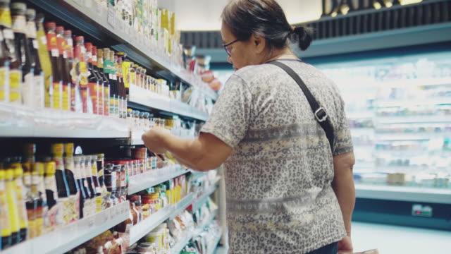 kvinna läser på condiment label - ingrediens bildbanksvideor och videomaterial från bakom kulisserna