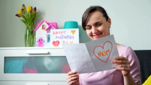 woman reading postcard on mothers day and smiling - mothers day stock videos & royalty-free footage