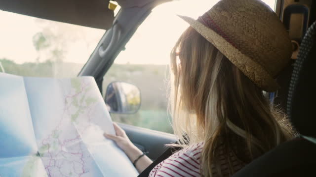 woman reading road map while sitting in car - viaggio in macchina video stock e b–roll
