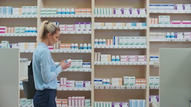 stockvideo's en b-roll-footage met ds vrouw het lezen van de achterkant van de geneeskunde fles nam ze de plank in de apotheek - paardenstaart haar naar achteren