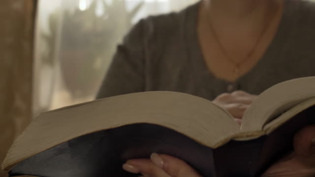 woman reads a book turns over the pages, bible, close video