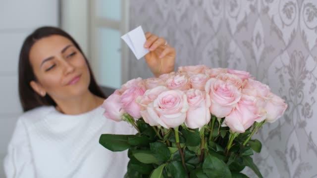 vidéos et rushes de la femme lit une carte dans des fleurs - composition florale