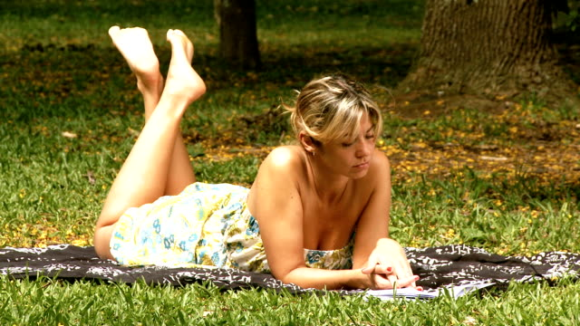 Woman reads on grass video