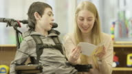 istock Woman Reads to Child with Physical Disability 526818318