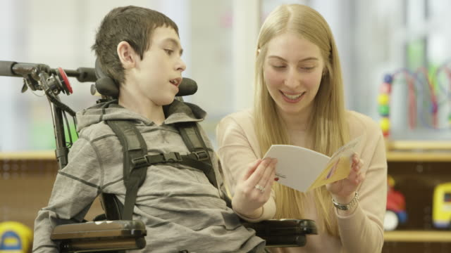 Woman Reads to Child with Physical Disability A child with a physical disability sits in a wheelchair and listens to a home caregiver read a book. disability stock videos & royalty-free footage
