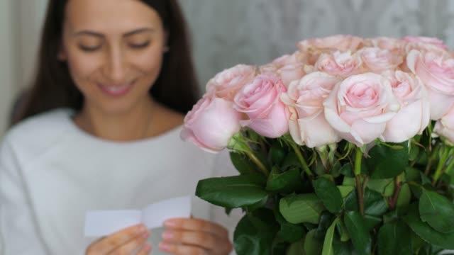 vidéos et rushes de la femme reçoit des fleurs avec le message - composition florale