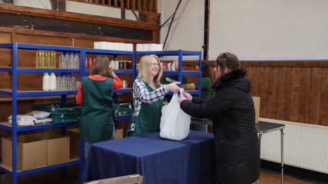vídeos y material grabado en eventos de stock de 4k: mujer recibe bolsa llena de alimentos banco de alimentos en una comida benéfica - food drive