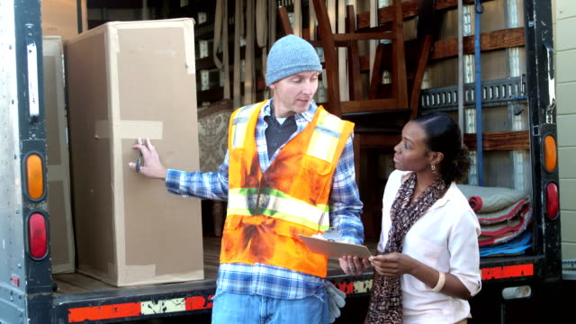 woman receiving delivery from truck driver - ricevere video stock e b–roll