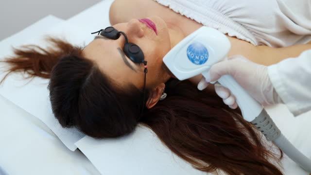 woman receiving epilation treatment - zabieg spa filmów i materiałów b-roll