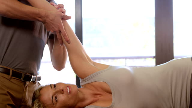 Woman receiving hand therapy exercises from physiotherapist video
