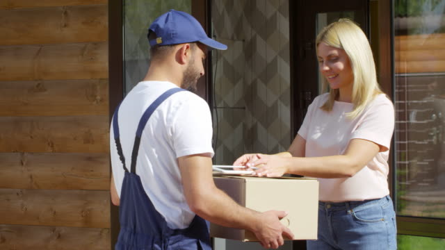 Woman Receiving Package and Signing Receipt on Tablet