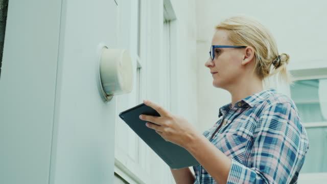 vidéos et rushes de une femme enregistre les lectures d'un compteur monté sur le mur d'une maison, utilise une tablette - inspecteur
