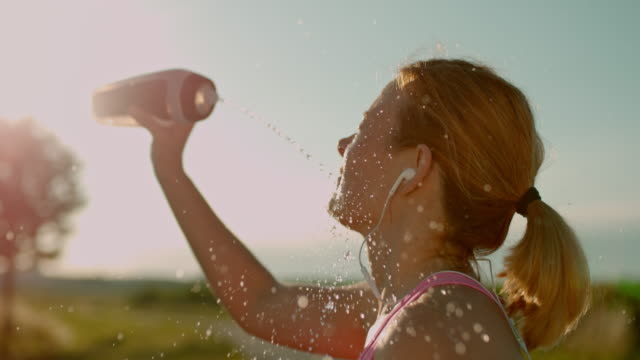 slo mo woman refreshing herself with splash of water - ritemprarsi video stock e b–roll