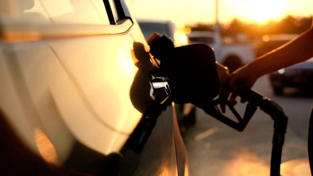 Woman refueling car at gas station pump at sunset