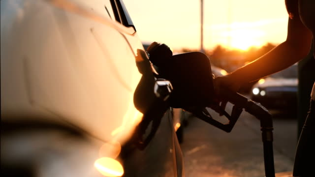 Woman refueling car at gas station pump at sunset