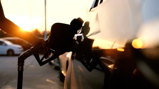 woman refueling car at gas station pump at sunset with flare - заправляться стоковые видео и кадры b-roll