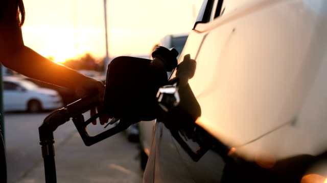 Woman refueling car at gas station pump at sunset with flare