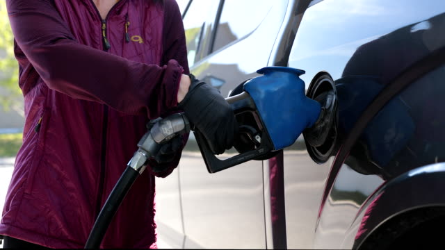 Woman Refueling Car at Gas Station With Protective Gloves During Covid-19 A woman is refueling her car at the gas station. She is holding the fuel pump with protective gloves during the Covid-19 pandemic to avoid being contaminated by the virus. This video is in slow motion. refueling stock videos & royalty-free footage