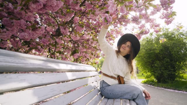 Woman relax in blooming garden Young girl relaxing on bench in spring nature park at sunny day. Wide-angle shot happy smiling woman in hat resting under blooming cherry tree while enjoying beautiful city garden in backlit park bench stock videos & royalty-free footage