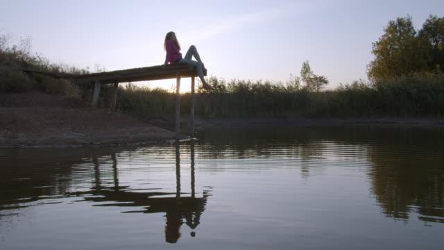 kvinnan slappnar av vid sjön sitter på kanten av en träbrygga, swing benen på solnedgången - flod vatten brygga bildbanksvideor och videomaterial från bakom kulisserna