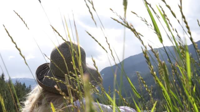 vidéos et rushes de la femme détend dans des herbes sur la pente de montagne - évasion du réel