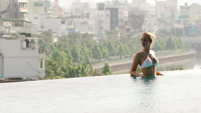 woman relaxes in infinity pool with view of city - cleavage stock videos & royalty-free footage