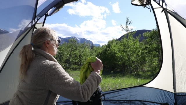 Woman relaxes in tent, mountain meadow