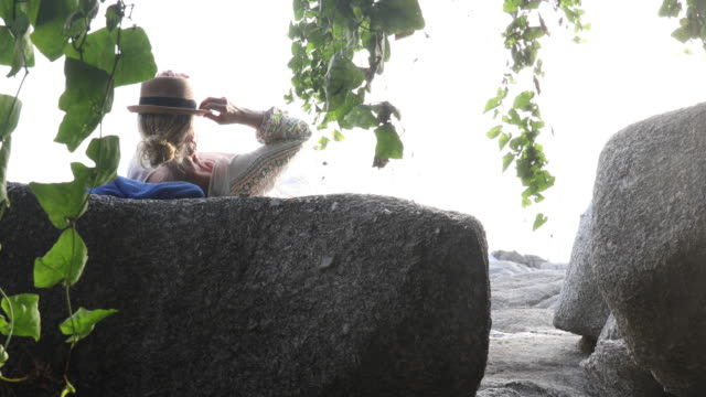 woman relaxes on granite boulder, wearing hat - эскапизм стоковые видео и кадры b-roll