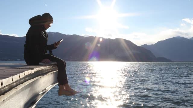 vídeos de stock e filmes b-roll de woman relaxes on lake pier at sunrise, texting - lago maggiore