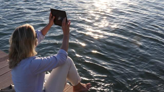 vídeos y material grabado en eventos de stock de mujer se relaja en el muelle del lago, toma foto con tableta digital - memorial day weekend