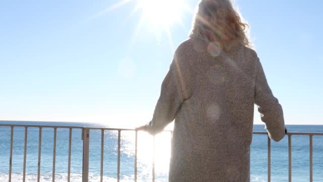 vidéos et rushes de femme se détend sur la rambarde au-dessus de mer au lever du soleil - évasion du réel