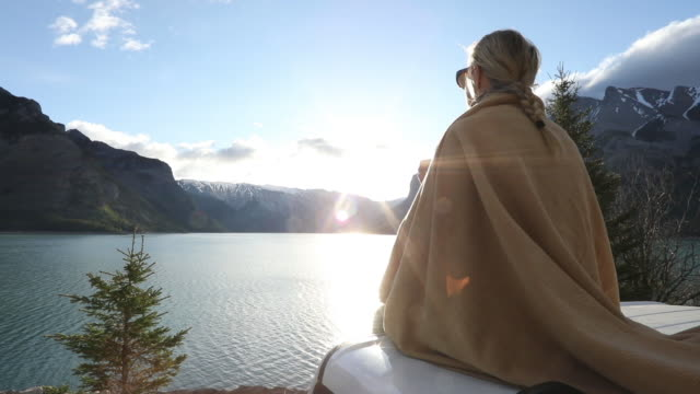Woman relaxes on vehicle hood/ cab at sunrise She looks out to view over lake. Mountains in distance blanket stock videos & royalty-free footage