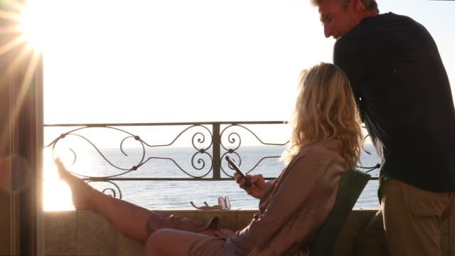 Woman relaxes on veranda, at sunrise, above sea