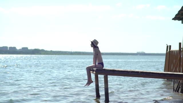 kvinna slappnar sitter på kanten av en träbryggan, ben swing nära vattenytan i bakgrunden - solar panel bildbanksvideor och videomaterial från bakom kulisserna