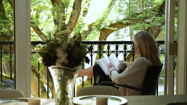 Woman relaxes with book and coffee on veranda, at sunrise