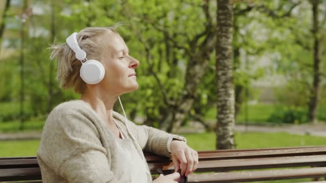 woman relaxing and listening to music in the park - садовая скамья стоковые видео и кадры b-roll