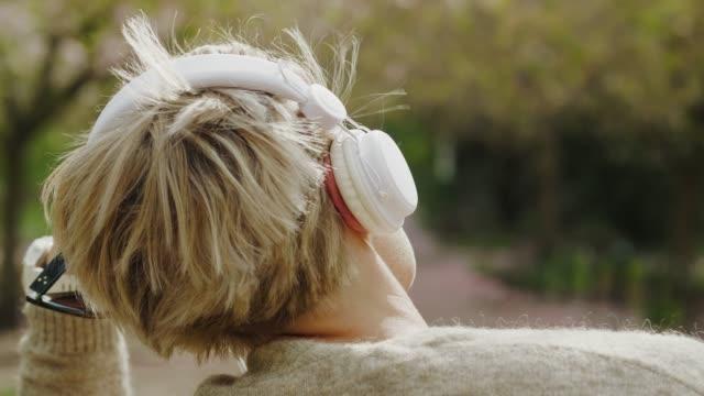 公園でリラックスして音楽を聴く女性 - ベンチ点の映像素材/bロール
