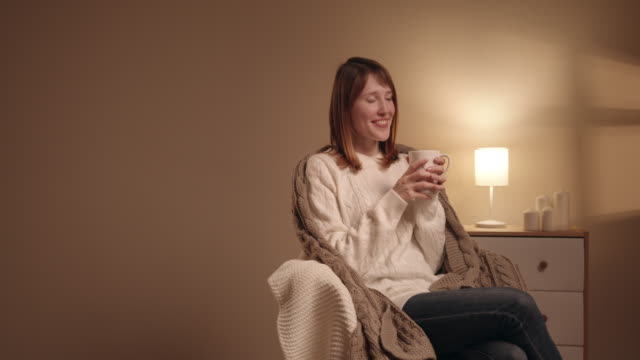 woman relaxing at home drinking a cup of coffee - время дня стоковые видео и кадры b-roll