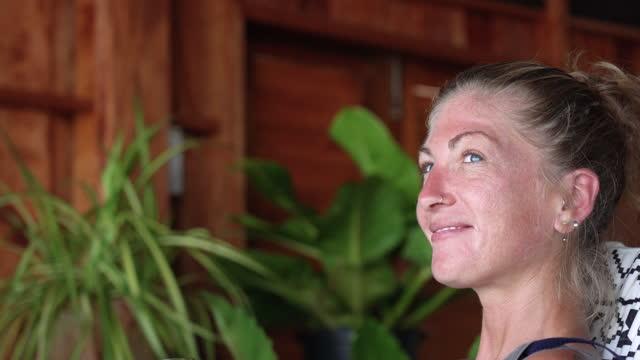 donna che si rilassa a casa con un bicchiere di vino tramonto - 35 39 anni video stock e b–roll