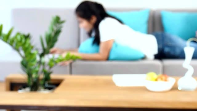 Mujer relajante de mentira abajo, libro de lectura del hogar - vídeo